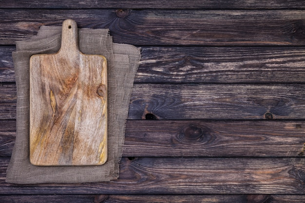 Vieille planche à découper sur une table en bois sombre. vue de dessus. espace de copie