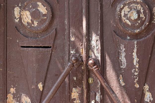 Vieille porte en bois marron minable avec poignée, gros plan, fond de campagne, orientation horizontale