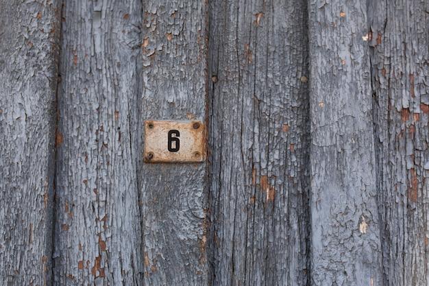 Vieille porte en bois avec peinture bleue écaillée et craquelée.