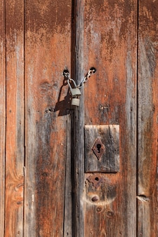 Vieille porte en bois avec serrure et chaîne.