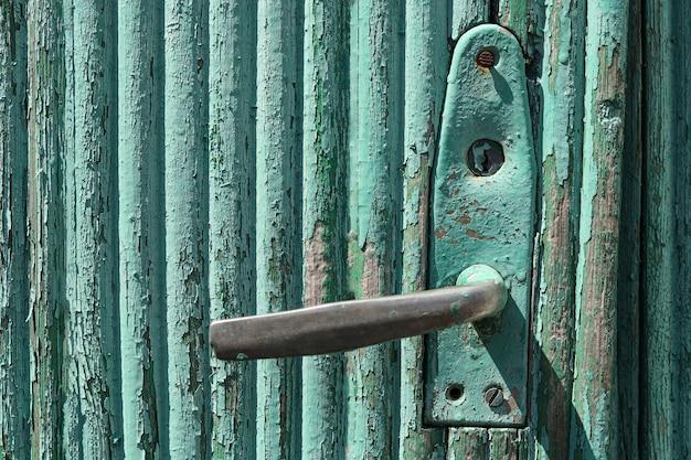 Vieille porte en bois verte minable avec poignée, fond de campagne rurale, espace de copie