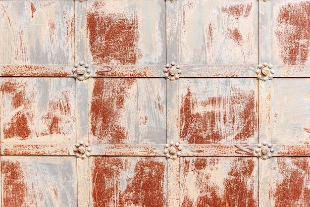 Vieille porte avec grille décorative et coups de peinture écaillée