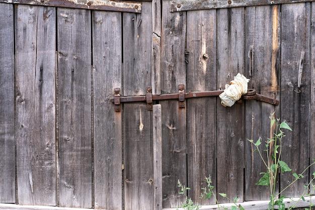 Une vieille porte verrouillée en bois et sale. contexte
