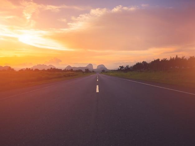 Vieille route contre des montagnes et un ciel nuageux pendant le coucher du soleil.