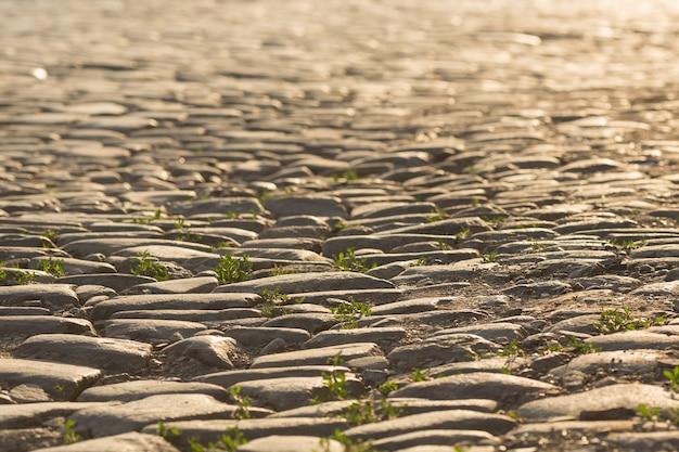 Vieille route en pierre avec de l'herbe au coucher du soleil