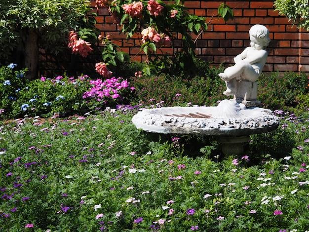 Vieille sculpture blanche et fleurs dans le parc.