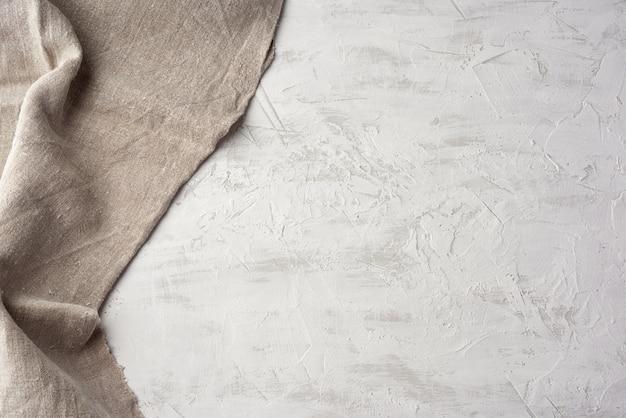 Vieille serviette de cuisine vintage gris sur fond de ciment blanc