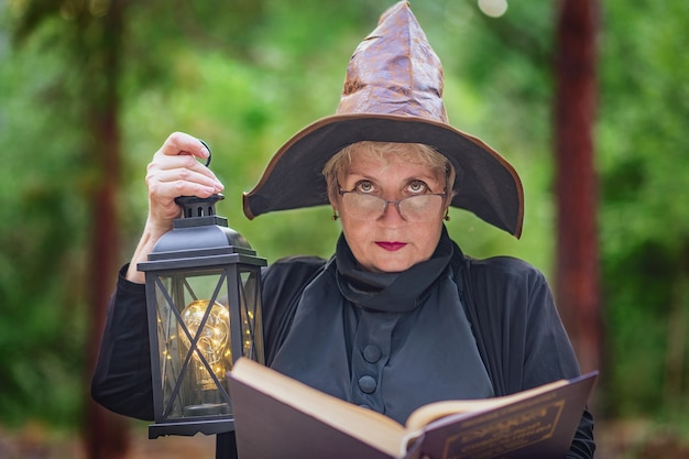 Une vieille sorcière à lunettes dans les bois, tenant un livre ouvert, l'éclairant avec une lampe antique.