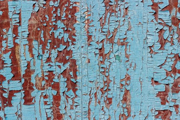 Vieille surface en bois de couleur marron avec des morceaux de peinture bleue qui s'écaillait