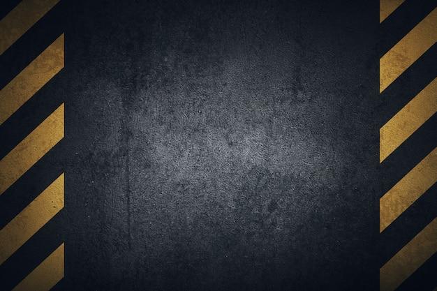 Vieille surface en tôle grungy noire avec des bandes d'avertissement jaunes.