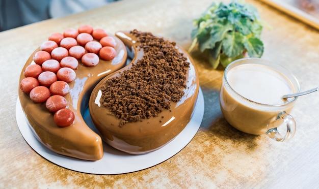 Sur une vieille table en bois, il y a un beau gâteau au chocolat mousse avec une grande tasse transparente avec du café aromatique et une plante d'intérieur