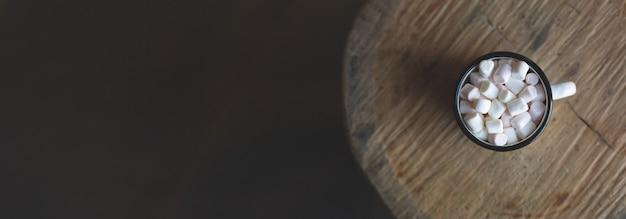Une vieille tasse en émail de noël remplie de cacao chaud et de guimauves