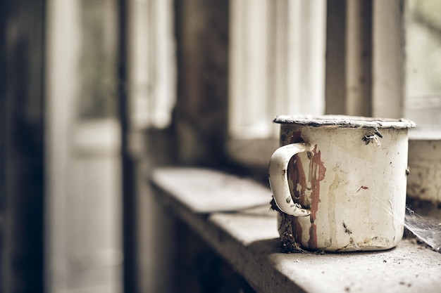 Vieille tasse en métal rouillée dans une vieille pièce poussiéreuse
