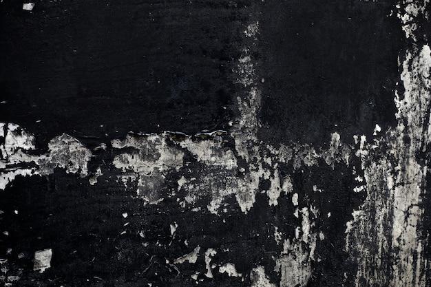 Vieille texture de peinture noire décollée du mur de béton