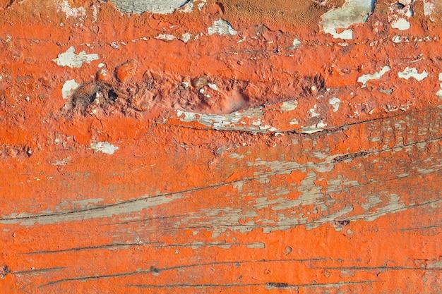 Vieille texture de peinture orange décollant de fond de planche de bois