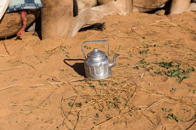 Vieille théière sur le sable dans le désert du sahara