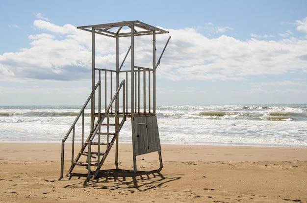Vieille tour de sauveteur vide sur la plage par temps nuageux.