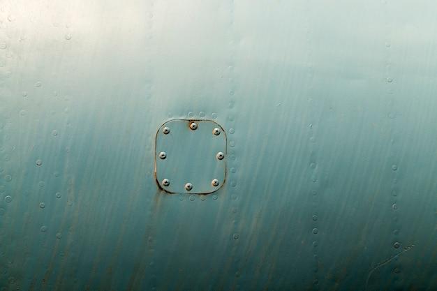 Vieille trappe en métal rouillé attaché par des rivets à une feuille de fer