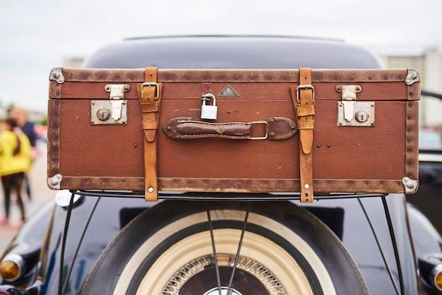 Vieille valise au-dessus de la roue sur le coffre d'une vieille voiture