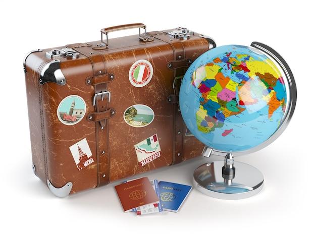 Vieille valise avec globe d'autocollants et passeports avec billets d'embarquement
