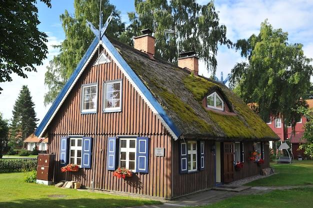 Vieille vieille maison en bois, rouge, dans le pays européen de la lituanie, dans la ville thermale de nida, sur la flèche de courlande.
