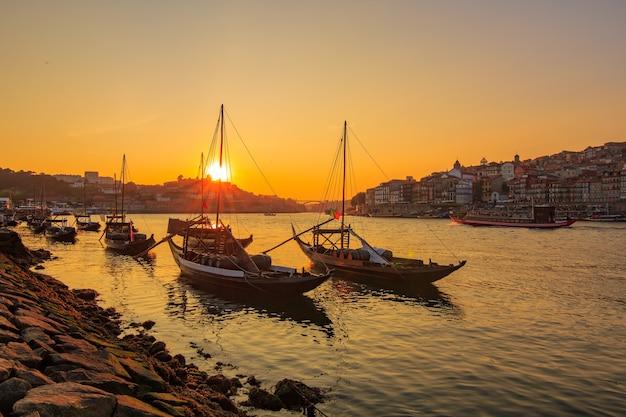 Vieille ville de porto et bateaux traditionnels avec des tonneaux de vin au coucher du soleil. le portugal.