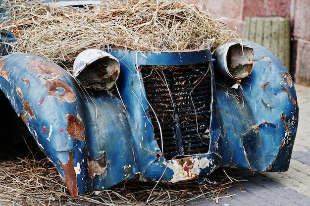 Vieille voiture abandonnée avec du foin sur le moteur