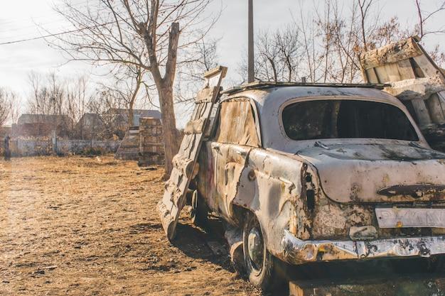 Vieille voiture endommagée sur l'arène de paintball