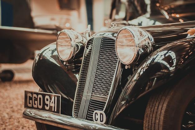 Vieille voiture rétro vue de face sur les phares et la calandre.