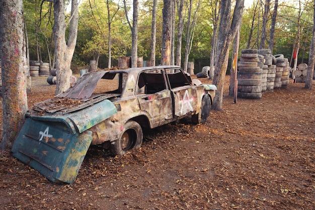 Une vieille voiture rouillée et abandonnée sur une base de paintball derrière laquelle se cachent les joueurs excités par le jeu