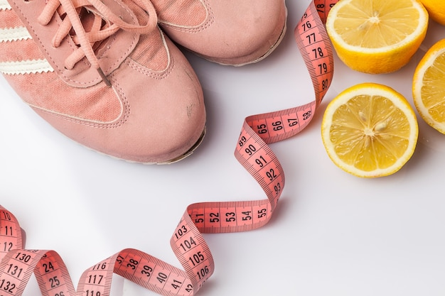 Les vieilles baskets, un mètre ruban et du citron sur fond blanc. concept de remise en forme et mode de vie sain
