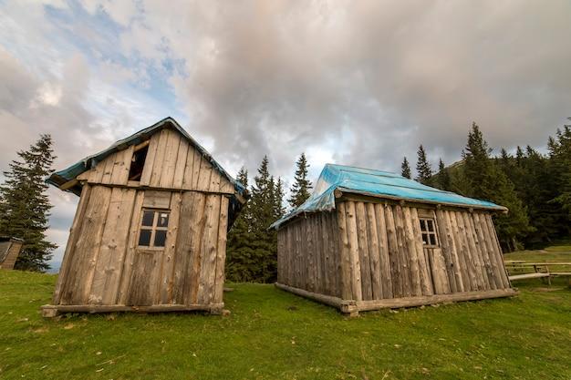 Vieilles cabanes de berger en bois sur la vallée verdoyante des montagnes.