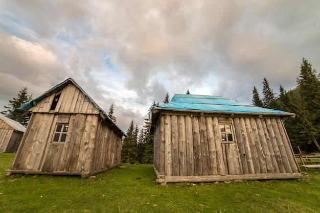 Vieilles cabanes de berger en bois sur la vallée verte de montagnes sur l'espace de copie bleu ciel nuageux.