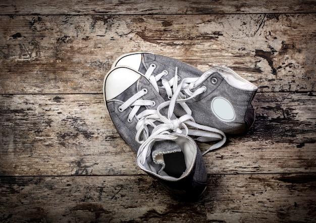 Vieilles chaussures grises sur fond de bois