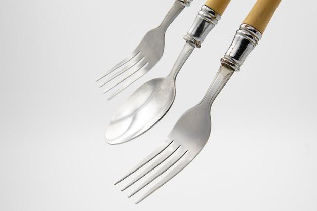 Vieilles fourchettes et cuillères vintage minable sur fond blanc