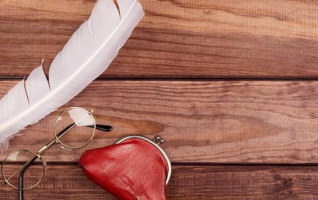Vieilles lunettes près de plume et sac vintage sur fond en bois