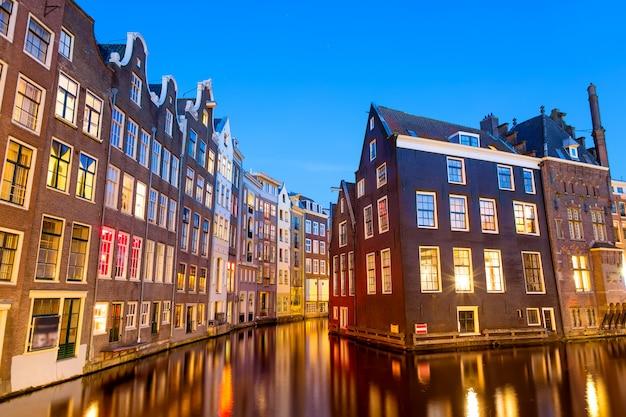 Vieilles maisons hollandaises typiques sur canal avec reflets au crépuscule à amsterdam, north hilland, pays-bas