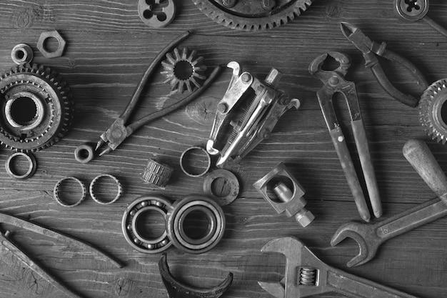 Vieilles pièces de voiture rouillées et vieux outils de réparation sur une table en bois.