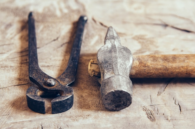 Vieilles pinces rouillées et marteau sur un fond en bois. un outil pour saisir et tirer des objets.
