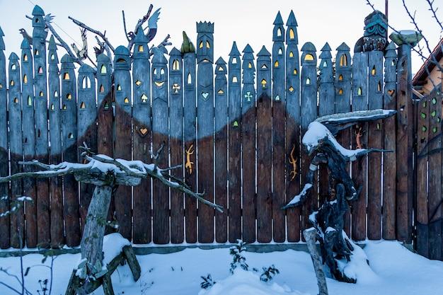 Vieilles planches d'une forme inhabituelle d'une clôture en bois avec verre coloré intégré