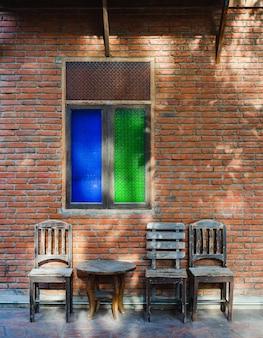 Vieilles tables et chaises en bois en face du mur de briques rouges vintage.