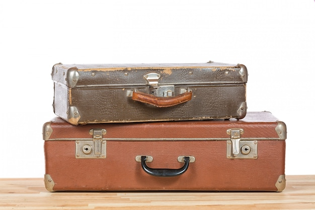 Vieilles valises vintage sur une table en bois clair isolée