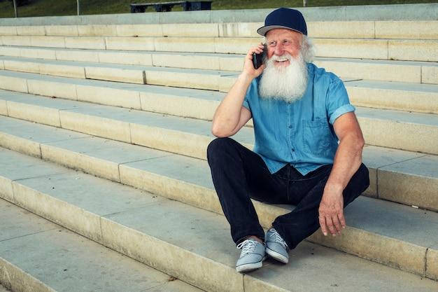 Vieillesse heureuse. vieil homme aux cheveux gris avec un sourire parlant au téléphone