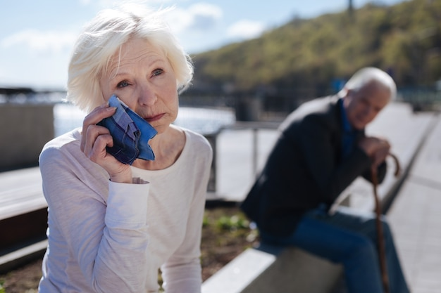 Vieillissement déçu femme ridée pleurer et regarder les avions tandis que le vieil homme la regarde