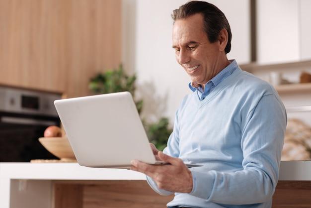 Vieillissement heureux homme heureux assis dans la cuisine tout en exprimant son bonheur et en travaillant avec un ordinateur portable