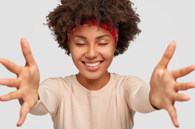 Viens entre mes mains. femme heureuse et sympathique aux cheveux bouclés, donne un câlin à quelqu'un, ferme les yeux avec plaisir, porte un pull décontracté, isolé sur un mur blanc.