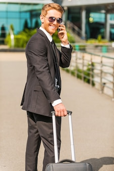 Vient d'arriver. gai jeune homme d'affaires en costume complet portant une valise et parlant au téléphone portable tout en marchant à l'extérieur