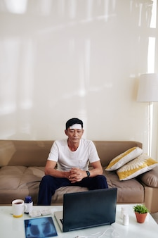 Vietnamien d'âge moyen avec un patch de fièvre rafraîchissante sur son front vidéo appelant son médecin