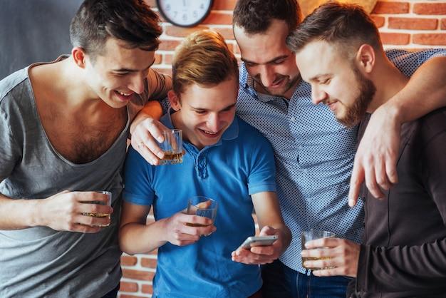 De vieux amis gais communiquent entre eux et se regardent au téléphone, des verres de whisky au pub. mode de vie de divertissement. wifi connecté en réunion de table