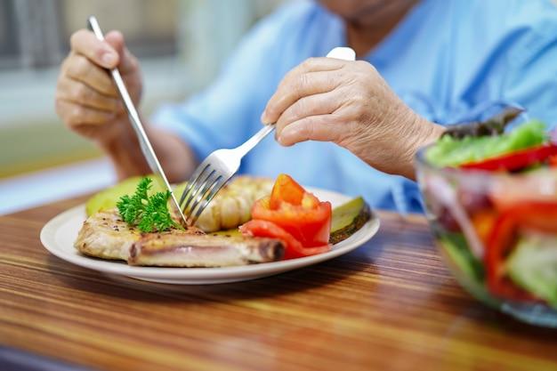 Vieux, asiatique, dame âgée, patiente, femme, manger, saumon, salade, légume, petit déjeuner, nourriture saine